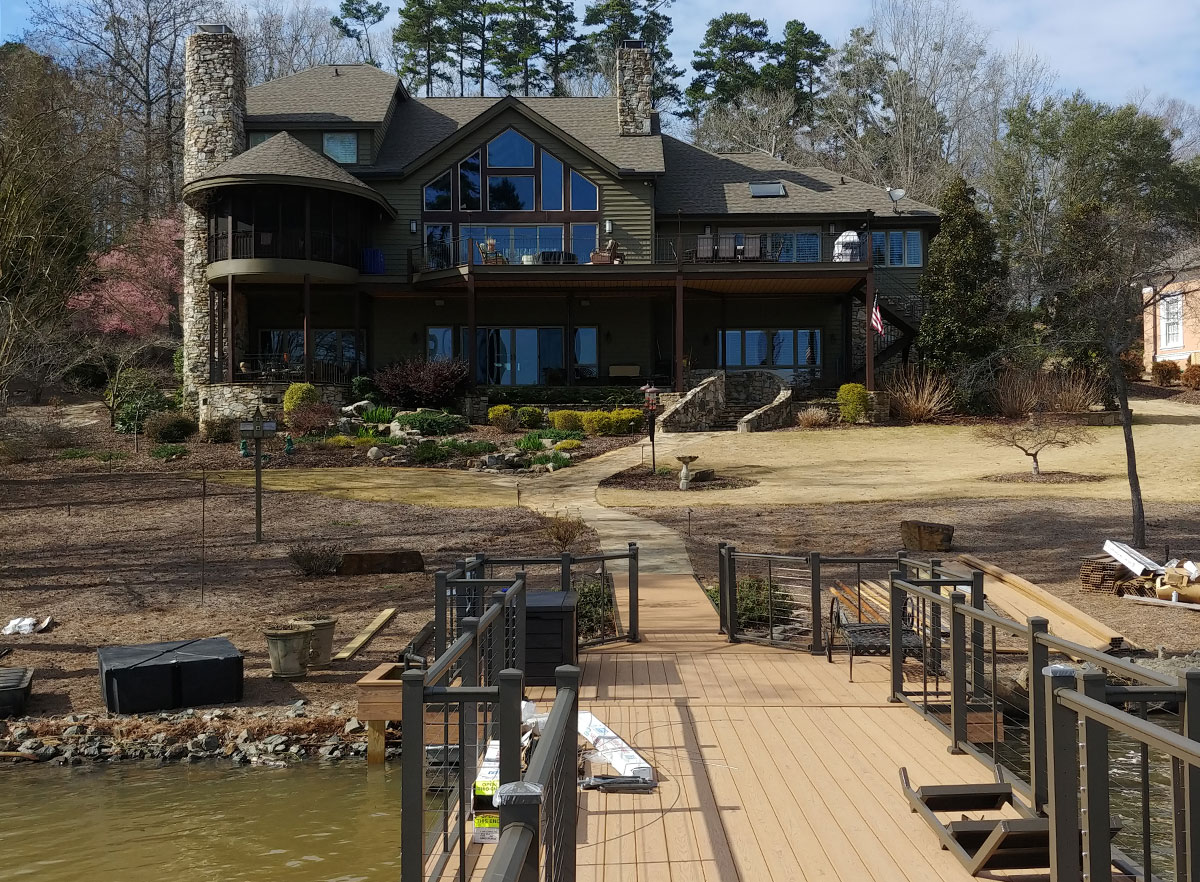Image of an extende walkway and dock to water from backyard of home; featuring DuxxBak Composite Decking compound.