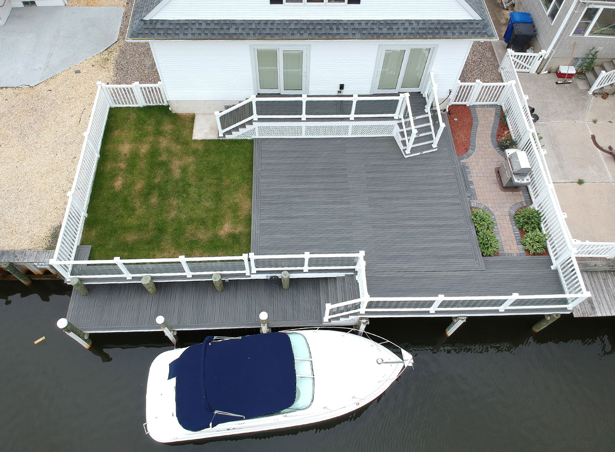 Overview view of a deck with access to navigable water featuring I.Dekk HD from DuxxBak Composite Decking.