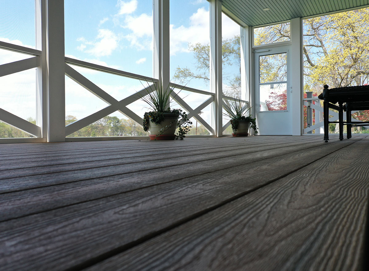 Optima Dekk featured in another screened in porch; composite decking in our armor cap finish .