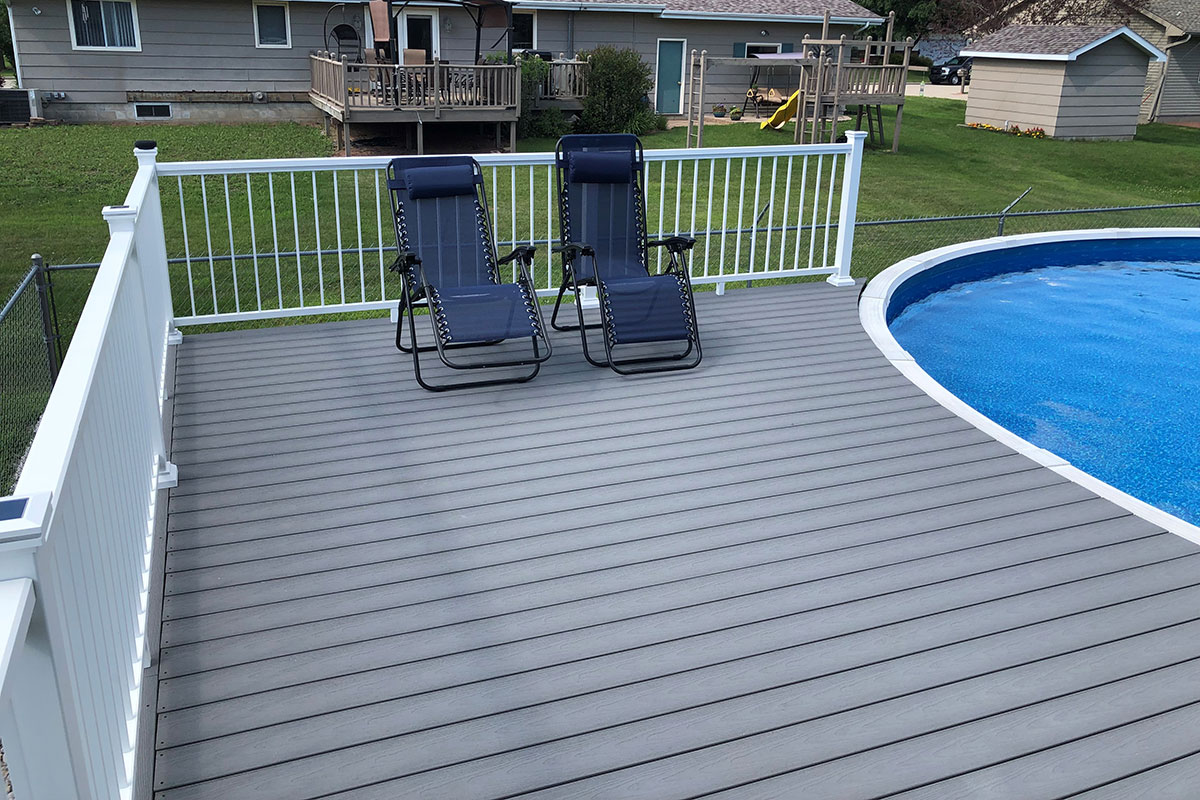 Image of a poolside composite deck build with Optima Dekk LT profile boards in a River Stone finish.